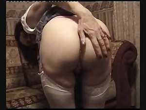 Mature slut strips and masturbates on the sofa