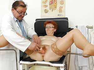 Redhead mature Jindriska is sitting with spread legs